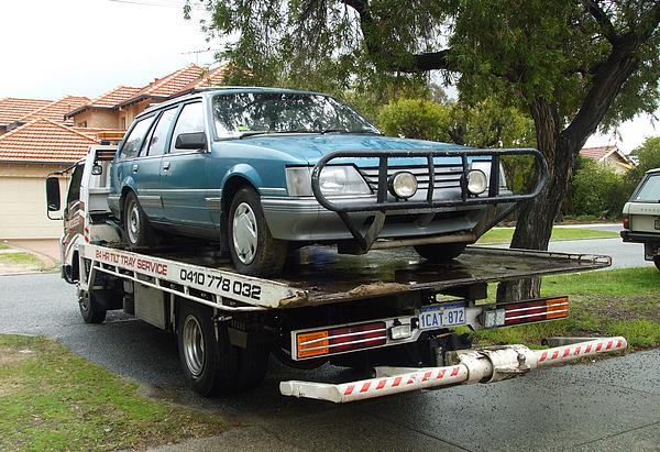 VK Commodore on tilt tray tow truck