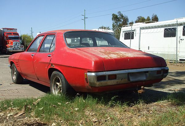 Red Holden HQ Sedan with mags